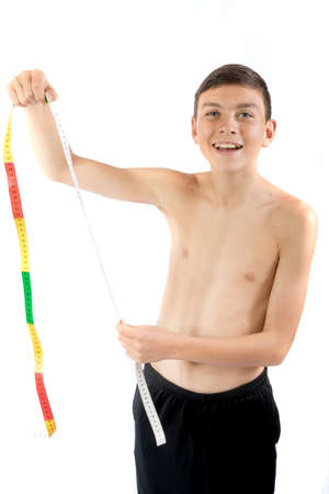 Teenage boy looking happy at a tape measure