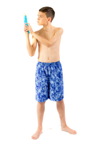Young teenage boy playing with water guns isolated on a white background Stock Photo