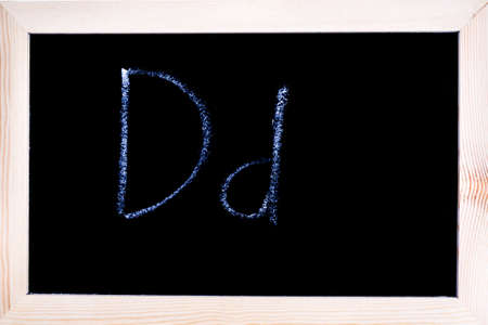 Blackboard with white chalk writing showing capital and lowercase D