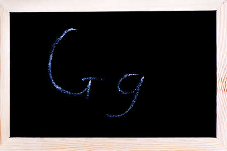 Blackboard with white chalk writing showing capital and lowercase G Stock Photo