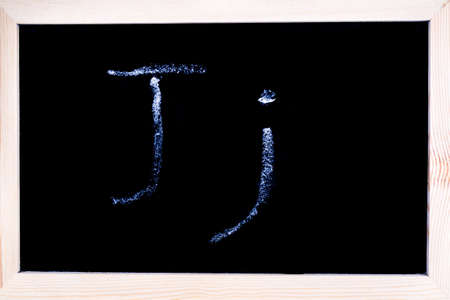Blackboard with white chalk writing showing capital and lowercase J Stock Photo