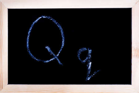 Blackboard with white chalk writing showing capital and lowercase Q