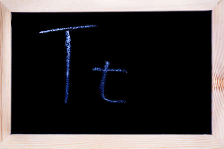 Blackboard with white chalk writing showing capital and lowercase T Stock Photo