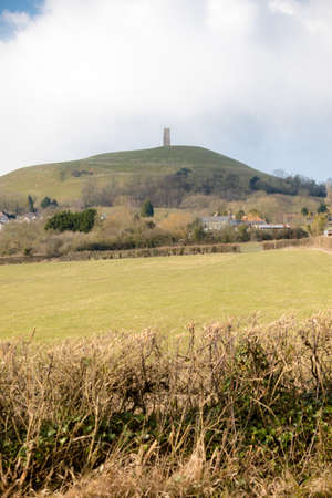 Glastonbury Tor in Somerset, United Kingdom, with the ruins of St Michaels Church demolished in 1539 during the Dissolution of the Monasteries Stock Photo