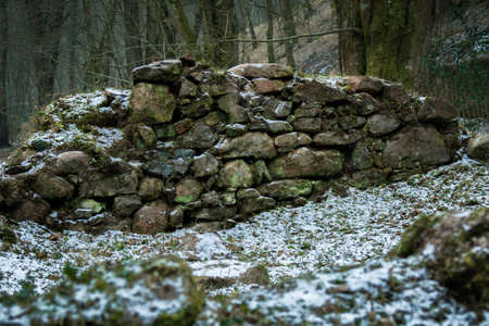 The ruins of an old stone watermill on Dartmoor, United Kingdom. The ruins have a light dusting of snow from the start of the Beast From The East winter storm of 2018