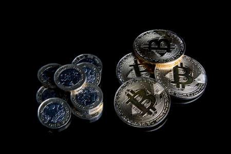 A bitcoin concept of bitcoins next to regular one poiund coins