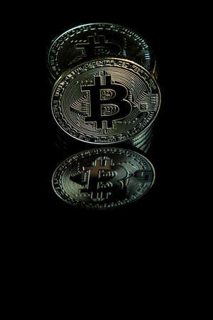 A bitcoin concept with tokens on a black background to represent the dark use of the currency Stock Photo