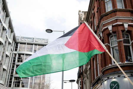 London, United Kingdom, 14th April 2018:- The flag of Palestine at a gathering of protesters along Kensington High Street, near the Israeli Embassy in London to protest the ongoing occupation of Palestine.