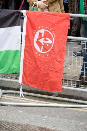 London, United Kingdom, 14th April 2018:- The flag of the PFLP at a gathering of protesters along Kensington High Street, near the Israeli Embassy in London to protest the ongoing occupation of Palestine. Banco de Imagens - 106325740