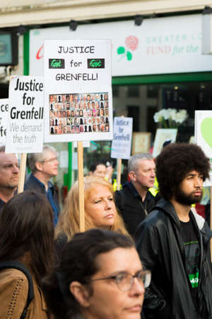 London, United Kingdom, 14th April 2018:- Marchers on a silent march from Kensington Town Hall to the ruins of Grenfell tower ten months on from the devastating fire that killed 71 Banque d'images - 105769218