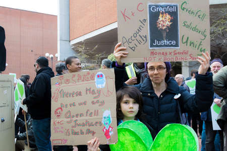 London, United Kingdom, 14th April 2018:- Marchers on a silent march from Kensington Town Hall to the ruins of Grenfell tower ten months on from the devastating fire that killed 71 Banque d'images - 105769245