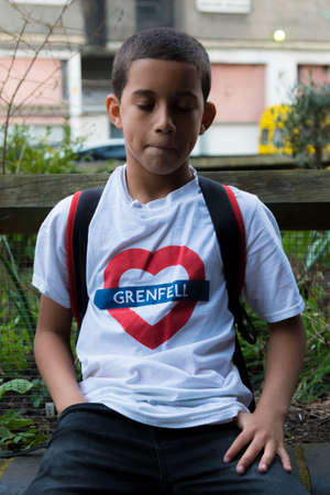 London, United Kingdom, 14th April 2018:- A young boy sits near the ruins of Grenfell tower ten months on from the devastating fire that killed 71 Éditoriale