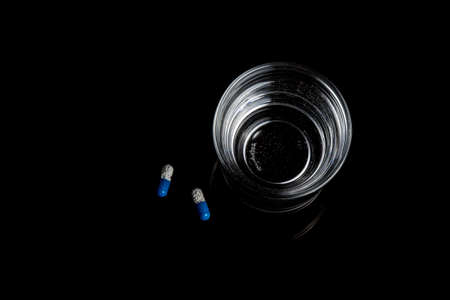 Medical pills next to a glass of water isolated  on a black background 免版税图像
