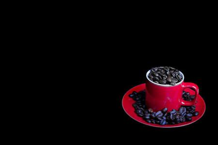 Whole roasted coffee beans and a coffee mug Фото со стока