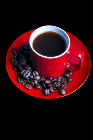 A mug of coffee with saucer and whole roasted coffee beans Фото со стока