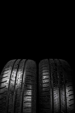 Close up view of a car tyre isolated on a black background with water drops 免版税图像