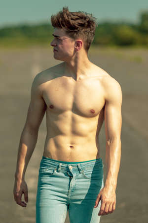 Young adult male standing outside shirtless on a warm summer's day Standard-Bild