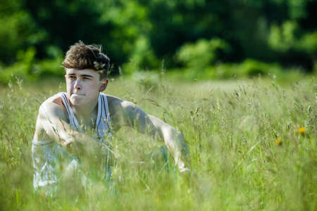 Young adult male sitting among long grass on a warm summer's day Stockfoto