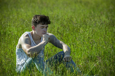 Young adult male sitting among long grass on a warm summer's day Reklamní fotografie
