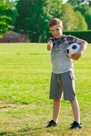 Pre-teen boy holding a football in a park Banque d'images