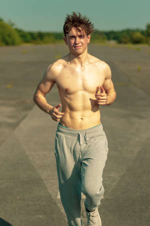 A young caucasian adult male jogging shirtless on a warm summer's day Foto de archivo