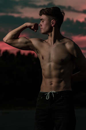 Young adult male flexing his arm muscles at twilight