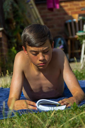 Teenage boy reading a book while sunbathing in a garden Stock fotó - 107260121