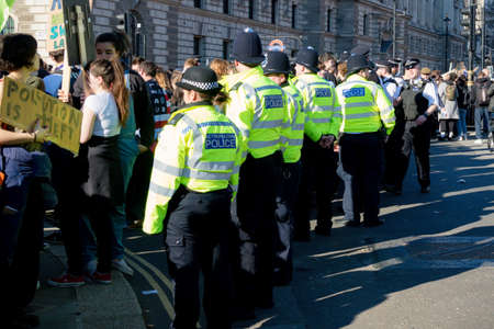 London, UK, United Kingdom 15th February 2019:- Striking school aged children in central London over climate change are watched by a line of police