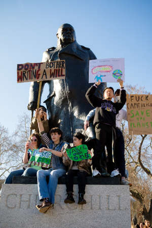 London, UK, United Kingdom 15th February 2019:- Striking school aged children in central London over climate change sit on the plith of the Winston Churchill statue in Parliament Square