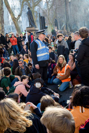 London, UK, United Kingdom 15th February 2019:- Striking school aged children in central London over climate change stage a sit down protest blocking roads around Parliament Square Éditoriale