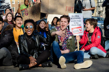 London, UK, United Kingdom 15th February 2019:- Striking school aged children in central London over climate change stage a sit down protest blocking Whitehall near Downing Street