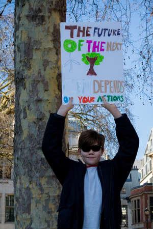 London, UK, United Kingdom 15th February 2019:- Striking school aged children in central London over climate change holding a placard Redakční