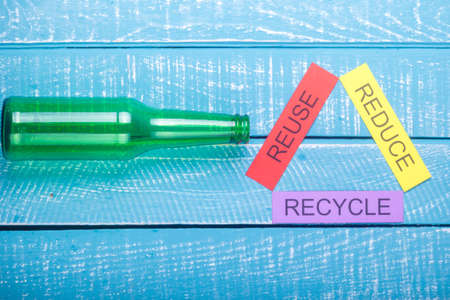 Recycle concept showing reduce, reuse, recycle with glass on a blue weathered background