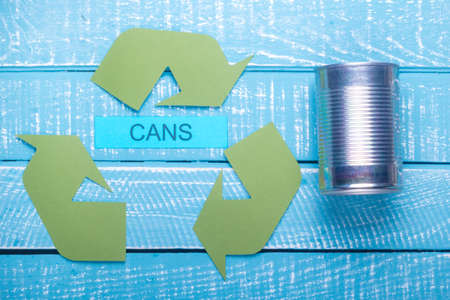 Recycle concept showing the green recycle logo with cans on a blue weathered background