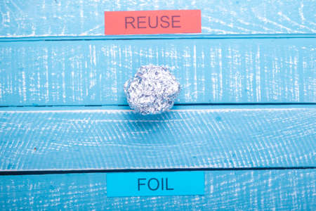 Recycle concept showing foil & reuse on a blue weathered background