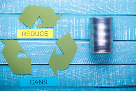 Recycle concept showing the green recycle logo with cans & reduce on a blue weathered background