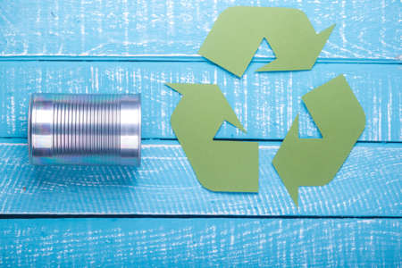 Recycle concept showing green recylce logo with cans on a blue weathered background