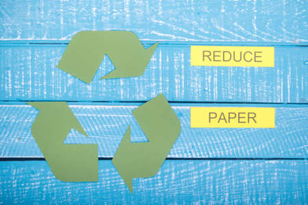 Recycle concept showing the green recycle logo with reduce paper on a blue weathered background