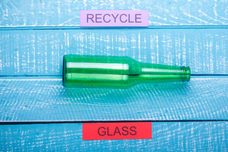Recycle concept showing glass & recycle on a blue weathered background