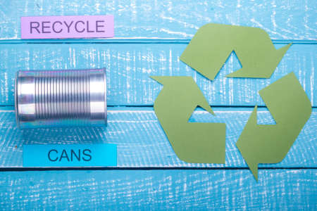 Recycle concept showing cans with the green recycle logo & recycle on a blue weathered background Stok Fotoğraf