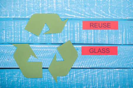 Recycle concept showing the green recycle logo with reuse glass on a blue weathered background