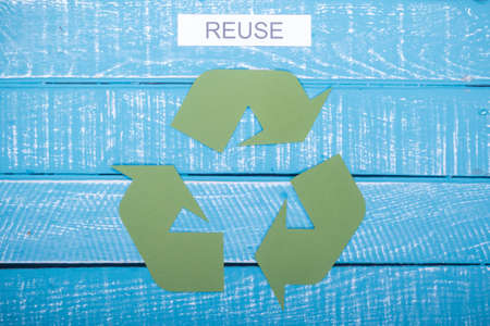Recycle concept showing the green recycle logo with reuse on a blue weathered background