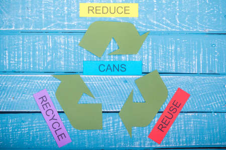 Recycle concept showing the green recycle logo with reduce,reuse,recycle & cans on a blue weathered background Stok Fotoğraf