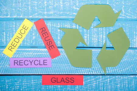 Recycle concept showing reduce, reuse, recycle and the recycle logo on a blue weathered background with glass