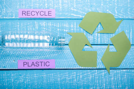 Recycle concept showing plastic with the green recycle logo & recycle on a blue weathered background Imagens