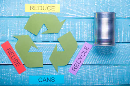 Recycle concept showing the green recycle logo with reduce, reuse, recycle & cans on a blue weathered background Stok Fotoğraf