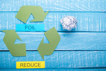 Recycle concept showing the green recycle logo with foil & reduce on a blue weathered background