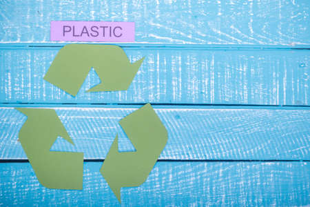 Recycle concept showing the green recycle logo with plastic and copy space on a blue weathered background