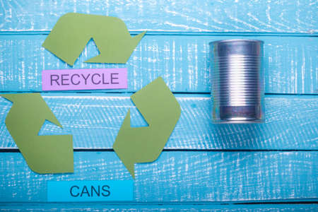 Recycle concept showing the green recycle logo with cans & recycle on a blue weathered background