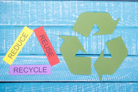 Recycle concept showing reduce, reuse, recycle and the recycle logo on a blue weathered background Stok Fotoğraf
